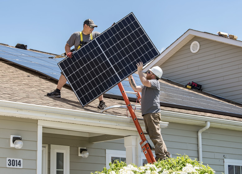Wyatt Whelan, left, and Eric Roberts, both PosiGen install supervisors, move a photovoltaic (PV) panel to a roof May 11, 2018, in the Dover Family Housing community at Dover Air Force Base, Del. Depending on the size of the housing unit, installation of the PV panels generally takes three to five days. (U.S. Air Force photo by Roland Balik)